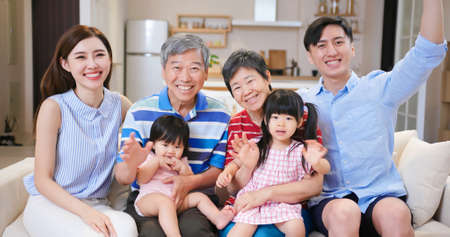 Photo pour asian family have video chat with computer happily at home - image libre de droit