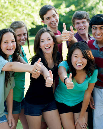 A multi-ethnic group of teenage friends outside with thumbsup