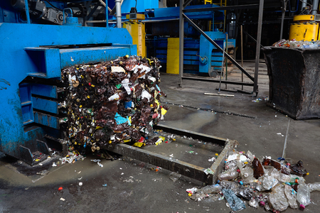 Photo pour Modern waste sorting and recycling plant, hydraulic press makes wired bale from pressed PET bottles for processing and reuse of plastic. Concept of defence of environment by materials reuse. - image libre de droit