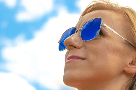 Photo pour Blonde womans close-up profile face with blue sunglasses and pink lipstick in blue sky with white clouds background with copy space - image libre de droit