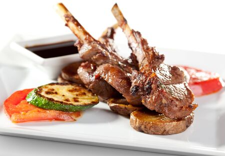 Roasted Lamb Chops  with Tomato and Zucchini Garnished with Sauce