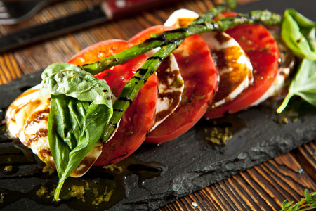Caprese Salad - Salad with Tomatoes, Mozzarella Cheese, Basil, Asparagus and Balsamic. Salad Dressing with Pesto Sauce