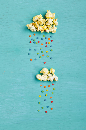 Photo for Weather Concept - Top View of Creative Popcorn Clouds with Colorful Sweet Rain on Blue Background. Minimal Concept. Flat Lay - Royalty Free Image