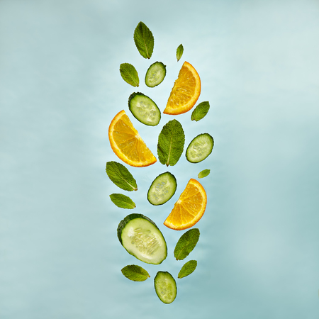 Summer Food and Drink - Fruit Lemonade Ingredient Pattern made of Cucumber, Orange and Mint. Splash Shape with Flying Drink Ingredient. Summer Fruit Drink Ingredient Concept. Flat Lay
