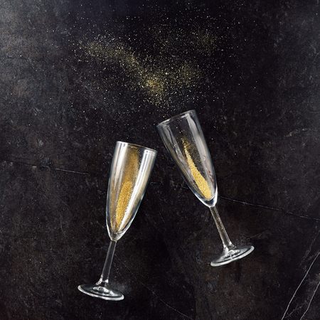 Foto de Merry Christmas and Happy New Year greeting card with champagne glass made of glitter sand on black slate background - Imagen libre de derechos