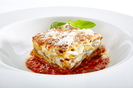 Photo pour Traditional Homemade Italian Lasagna with Tomato Sauce Isolated on White Background. Hot Tasty Lasagna or Lasagna with Parmesan Cheese on Elegant Restaurant Plate Close Up - image libre de droit