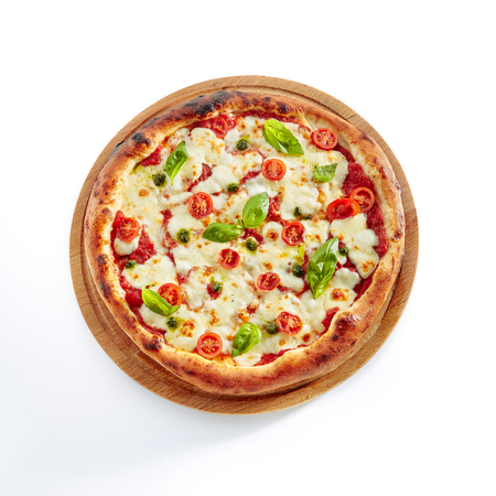 Foto de Pizza Margarita or Margherita with Cherry Tomatoes, Mozzarella Cheese, Pesto and Tomato Sauce Isolated on White Background. Traditional Italian Whole Yeasted Flatbread on Wooden Plate Close Up - Imagen libre de derechos