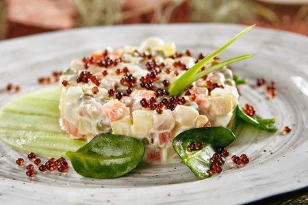 Photo pour Olivier Salad or Russian Salad with Salmon and Caviar on Retro Ceramic Plate. - image libre de droit