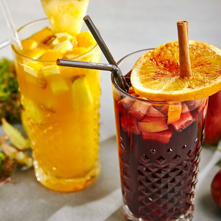 Photo pour Set of hot autumn cocktails with red and white spicy mulled wines. Apple cinnamon spiced fall mulled wine and warm tropical gluhwein with pineapple and orange in transparent glass cups on grey table - image libre de droit