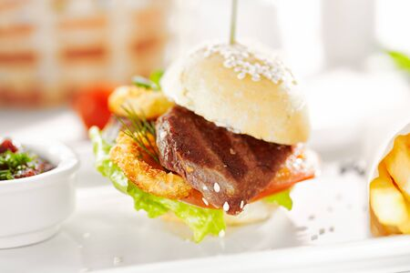 Photo pour Gourmet, restaurant, delicious dinner food - close up of Sandwich with Beef and Deep Fried Onions Ring, Tomato and Cucumber. Garnished with French Fries - image libre de droit