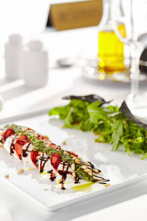 Photo pour Gourmet, restaurant, delicious dinner food - close up of Caprese Salad. Salad with Tomatoes, Mozzarella Cheese, Balsamic. Salad Dressing with Pesto Sauce and Rocket Salad - image libre de droit