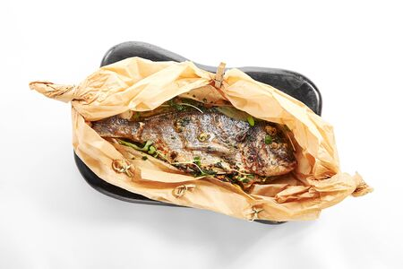 Photo pour Baked dorado fish in parchment. Grilled tuna in black plate. Cooked dolphinfish with herbs. Served seafood restaurant food. Marine delicacy, mediterranean delicious gourmet meal - image libre de droit