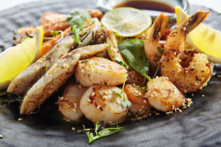 Photo pour Teppanyaki Style Seafood - Grilled Mixed Seafood with Soy Sauce and Vegetables. Japanese Teppanyaki Salmon Steak, Shrimp, Scallop and Fish Fillet garnished with lemon and green salad - image libre de droit
