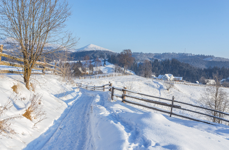 Photo pour Winter country landscape with timber fence and snowy road into evergreen forest - image libre de droit