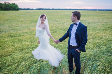 Photo pour young bride and groom on the background of the field - image libre de droit