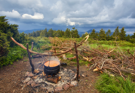 Photo pour Kettle on fire in the forest during hike or trekking in nature. The concept of camp food - image libre de droit