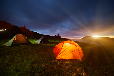 Photo pour Yellow Illuminated Tent in the Beautirul Evening Mountains. Adventure and Travel Concept. - image libre de droit
