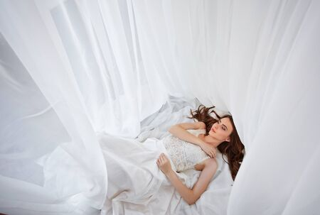 Photo pour Stylish bride lying in bed. Woman stretching in bed, wake up. Morning Meeting. flat lay. top view. - image libre de droit