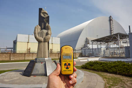 PRIPYAT, UKRAINE - April 25 2019: Monument to the Chernobyl Liquidators and fourth reactor without enclosing sarcophagus. Chornobyl Nuclear Power Plant - ChNPP