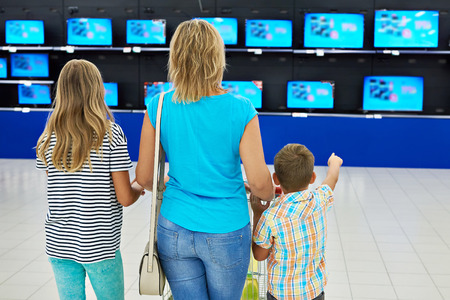 Mother with children in shop of household appliances