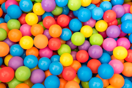 Many colorful plastic balls in a kids' ballpit at a playground.