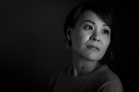 A black and white headshot of a sad looking middle aged Japanese woman.