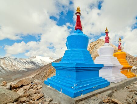 close up of three colorful stupas at the top of hill