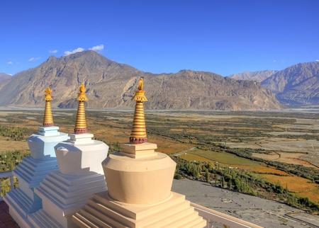 close up of three buddhist stupas at hill top