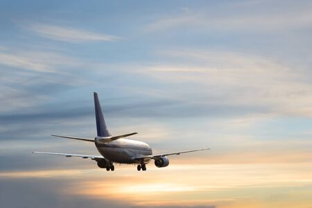 Photo pour Airplane with landing gear in cloudy sky at sunset or sunrise  - image libre de droit