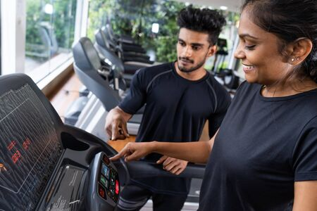Photo pour Well qualified trainer explains to his client how to use treadmill, wearing black t shirt and red sports jacket. Beautiful brunette lady follows all instructions, being concentrated and attentive. - image libre de droit