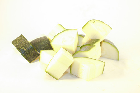 A pile of zucchini cubes, isolated on white background