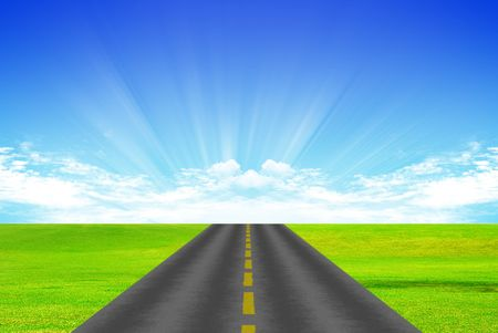 Road with yellow dividing stripon background of green grass and blue sky