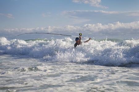 Photo pour Surf fisherman into the waves. Surf casting fishing - image libre de droit