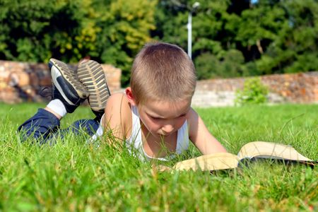 The child attentively reads the book on a summer meadow