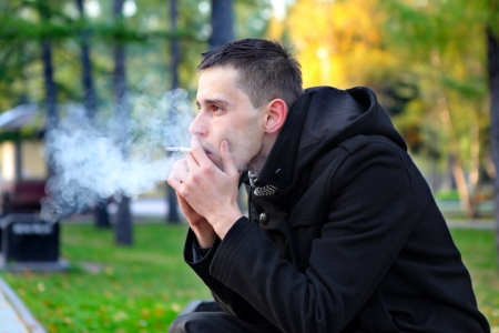 Sad man smoking cigarette in the autumn park
