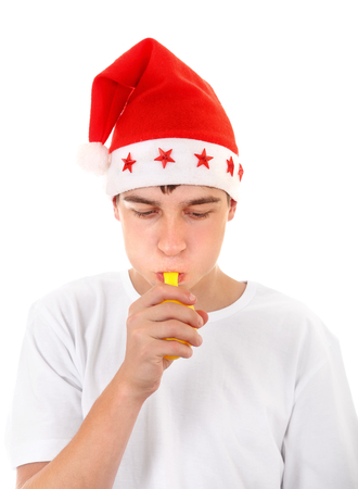 Teenager in Santa's Hat trying to inflate a Balloon Isolated On The White Background