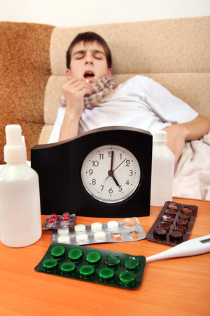 Focus on the Clock. Sick Teenager taking a Pill on the Bed at the Home