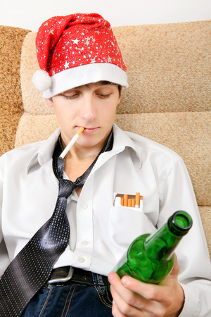 Teenager in Santa Hat with Bottle of the Beer smoking Cigarette