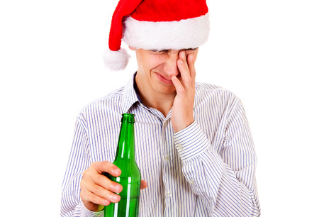 Tired Young Man in Santa Hat with a Bottle of the Beer Isolated on the White Background