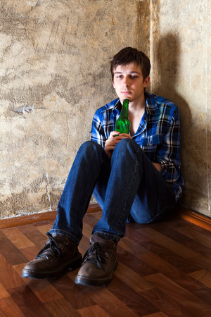 Sad Young Man with a Beer in the Corner by the Old Wall