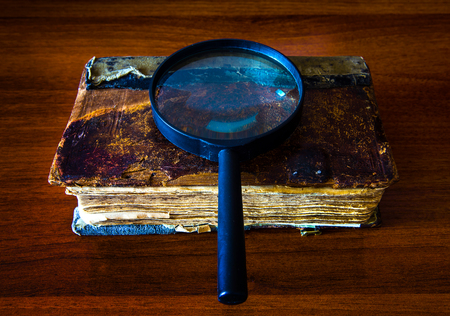 Photo pour Old Book with a Magnifying Glass on the Table closeup - image libre de droit