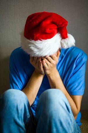 Photo pour Sad Man in Santa Hat hide a Face by the Wall - image libre de droit