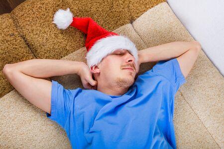 Foto de Young Man in Santa Hat sleeping on the Sofa at the Home - Imagen libre de derechos