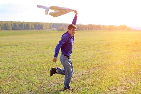 Photo pour Happy Young Man running on the Grass of the Summer Field - image libre de droit