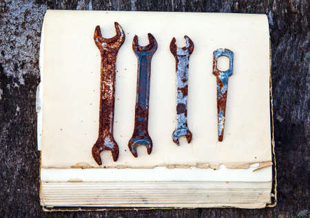 Photo pour Old Rusty Tools on the Old Book and Wooden Background closeup - image libre de droit