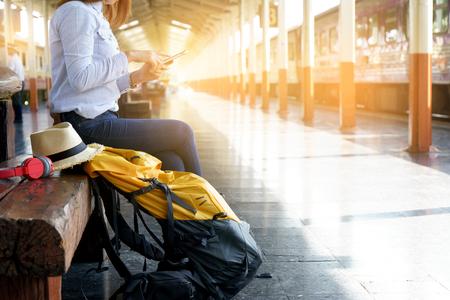 Foto de woman with her backpack sitting in train station for start her travel program - Imagen libre de derechos