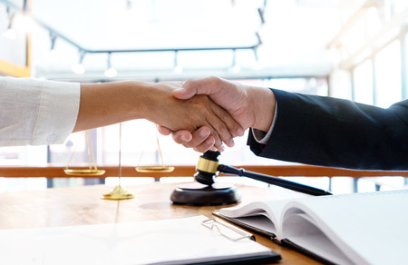 Foto de Lawyer or judge  with gavel and balance handshake with client or customer about agreement how to  use arbitration       handshake - Imagen libre de derechos