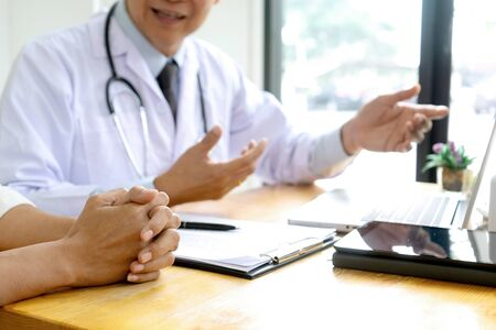 professional doctor sit at the table and talk about health care to the patient, on the table there are bottle of medicine.