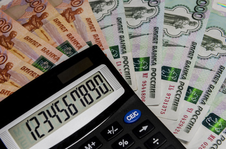 Calculator on background banknote 1000 and 5000 rubles.