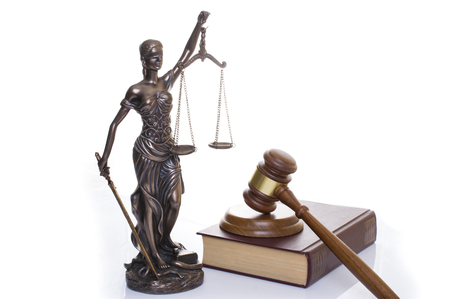 Foto de statue of justice, judges hammer behind books on a white background - Imagen libre de derechos